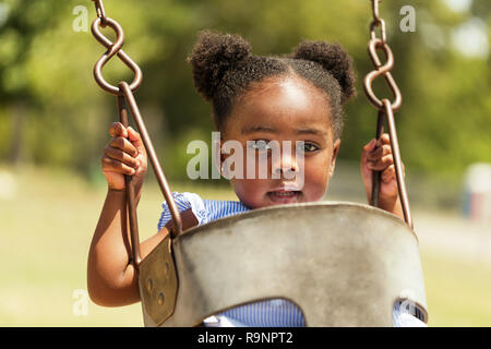 Cute little African American swinging at the park. - Stock Photo