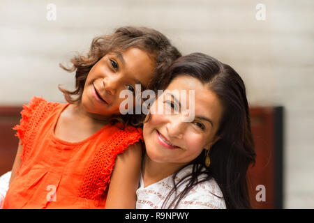 Loving mom smiling hugging her young daugher. - Stock Photo