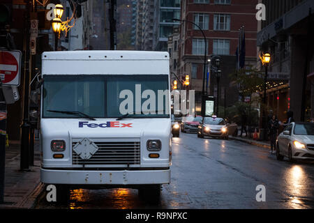 MONTREAL, CANADA - NOVEMBER 5, 2018: Fedex logo on one of their delivery trucks in a street of Montreal, Quebec. Fedex is an American courier speciali - Stock Photo