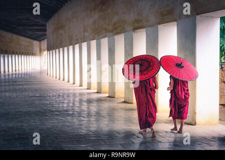 Two buddhist monk novice holding red umbrellas and walking in pagoda, Myanmar. - Stock Photo