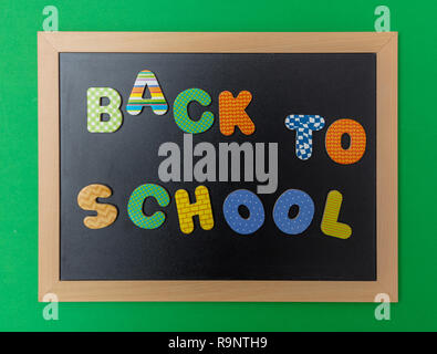 School concept. Black chalkboard with wooden frame,  text back to school in colorful letters, green wall background - Stock Photo