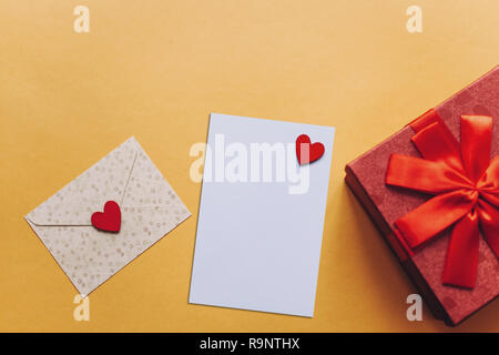 Blank sheet with red heart for text or write. Near an envelope with a heart to send and a box with a gift. Concept for Valentine's Day or Women's Day or Mother's Day. - Stock Photo