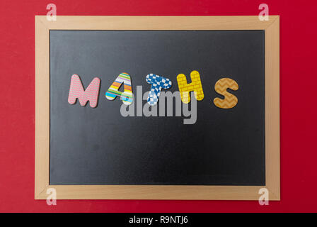 School maths concept. Black chalkboard with wooden frame, word, text maths in colorful letters, red wall background - Stock Photo