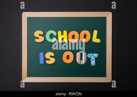 School is out concept. Green chalkboard with wooden frame, text school is out in colorful letters, black wall background - Stock Photo