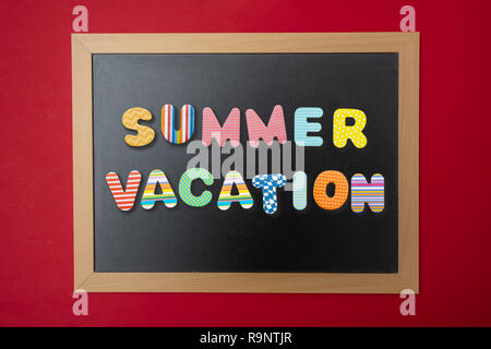 Summer vacation concept. Black chalkboard with wooden frame, text summer vacation in colorful letters, red wall background - Stock Photo