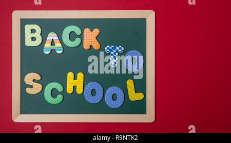 School concept. Green chalkboard with wooden frame,  text back to school in colorful letters, red wall background, copy space - Stock Photo