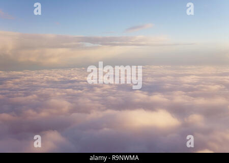 Sky with clouds at sunset from inside the plane landscape - Stock Photo