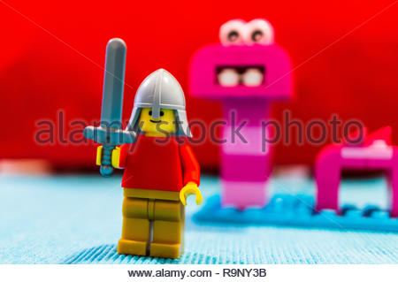Poznan, Poland - December 26, 2018: Lego knight with sword standing close by a pink monster in soft focus background. - Stock Photo