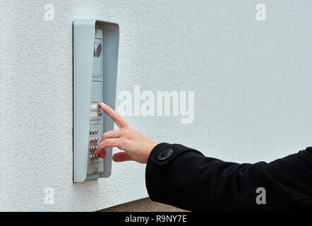 The female hand presses a button doorbell with camera and intercom - Stock Photo