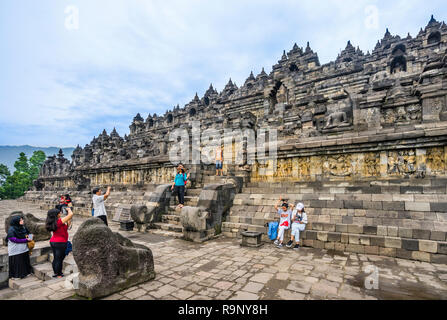 visitors at the ascent to the mandala step pyramid of 9th century Borobudur Buddhist temple, Central Java, Indonesia - Stock Photo