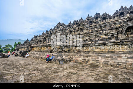 visitors resting at the base terrace of the mandala step pyramid of 9th century Borobudur Buddhist temple, Central Java, Indonesia - Stock Photo