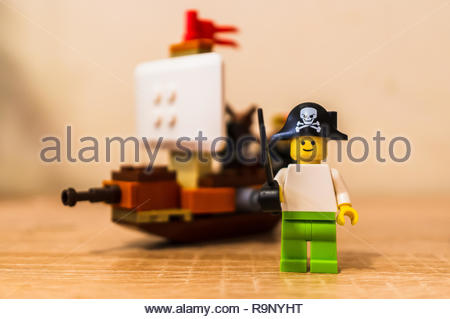 Poznan, Poland - December 26, 2018: Lego toy pirate holding a sword and standing in front of a ship in soft focus background. - Stock Photo