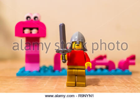 Poznan, Poland - December 26, 2018: Lego warrior holding a sword with monster in soft focus background. - Stock Photo