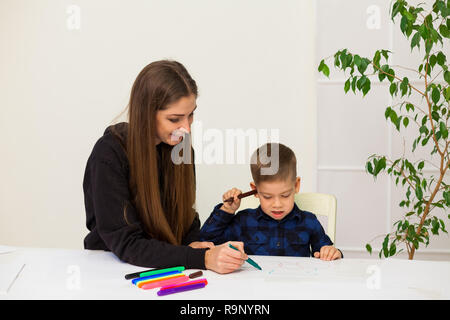 woman teaches a young boy paint markers - Stock Photo