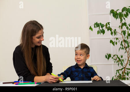 mom teaches young boy son to draw markers at the table - Stock Photo