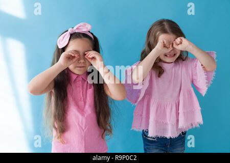 two little girls girlfriends sisters portrait on a blue background