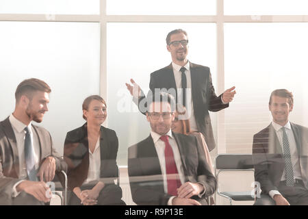 businessman standing to address colleagues at meeting - Stock Photo
