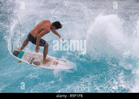 Young athletic surfer riding a wild wave at Honolua Bay on Maui. - Stock Photo