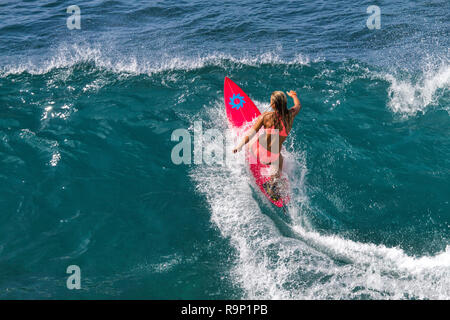 Young athletic female surfer riding a big wave at Honolua Bay on Maui. - Stock Photo