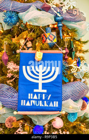 Christmas tree is beautifully decorated with colorful toys, garlands, stars, a candlestick and a flag with the inscription Happy Hanukkah. - Stock Photo