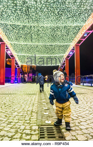 Poznan, Poland - December 26, 2018: Toddler boy standing on the Jordan bridge with Christmas lamps by night. - Stock Photo