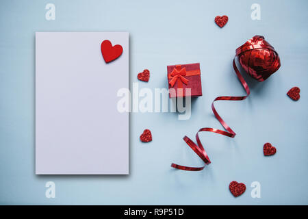 Festive background with a box with a gift and a lot of hearts and ribbon. Next is a white sheet of paper with a heart for text. Concept for Valentine's Day or Women's Day or another love event. - Stock Photo