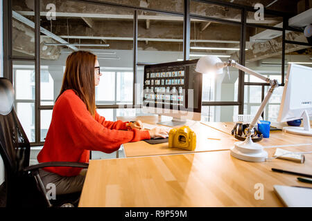 Woman working as a photographer editing photos with computer sitting at the working place in the modern office interior - Stock Photo