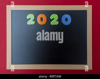 2020 New year. Black chalkboard with wooden frame, number 2020 in colorful numbers, red wall background, copy space - Stock Photo