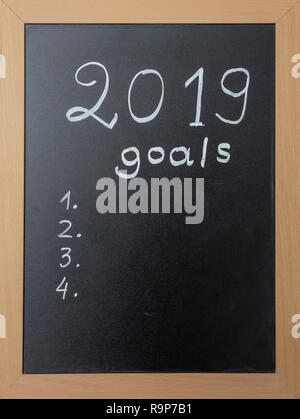 2019 New year goals. Black chalkboard with wooden frame, handwritten text 2019 goals, copy space - Stock Photo