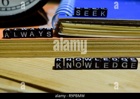 Always seek knowledge written on wooden blocks. Education and business concept on wooden background - Stock Photo