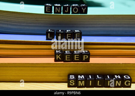 Enjoy life keep smiling written on wooden blocks. Education and business concept on wooden background - Stock Photo