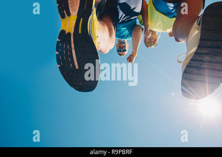 Bottom view cropped image of two people in sneakers while running - Stock Photo