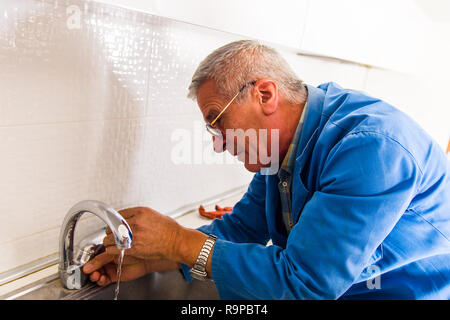 Repairman in blue working suit repair kitchen faucet - Stock Photo