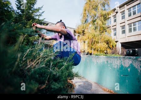 Young parkour guy jumping over a concrete wall and landing on another concrete wall while doing tricks in the air. - Stock Photo