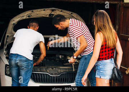 Three friends checking motor oil  on car engine - Stock Photo