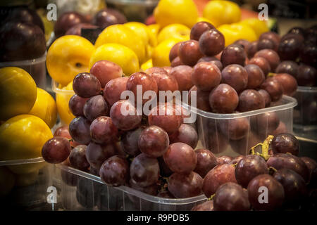 Plastic boxes with red grape and other fruit on a marketplace stall - Stock Photo