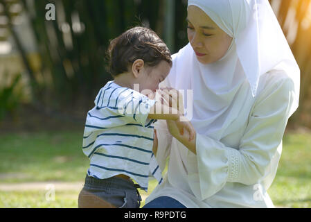 malay muslim mother and boy throwing tantrum - Stock Photo