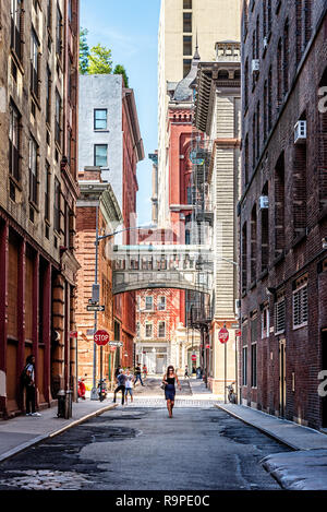 New York City, USA - June 25, 2018: Woman walking on Staple Street in Tribeca. This alley runs two blocks north between Duane and Harrison Streets, ju - Stock Photo