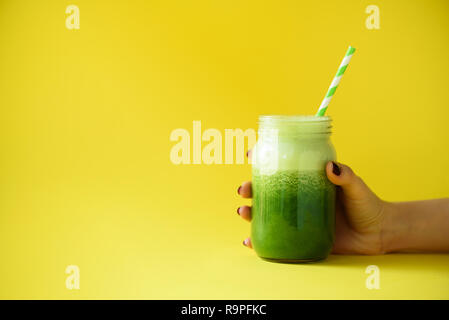 Woman hand holding glass jar of green smoothie, fresh juice against yellow background. Healthy beverage, vegan, vegetarian concept. Banner with copy s - Stock Photo