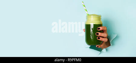 Woman hand holding glass jar of green smoothie, fresh juice against blue background. Healthy beverage, vegan, vegetarian concept. Banner with copy spa - Stock Photo
