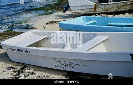 Boats on a Caribbean islands rock shoreline pulled up onto the white sand beach - Stock Photo