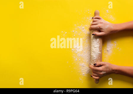 Girl hands keep rolling pin with flour on yellow background. Bake menu, recipe, homemade pastry concept. Top view. Banner with copy space for your tex - Stock Photo