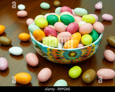 Bowl full sugar coated almonds on the table - Stock Photo