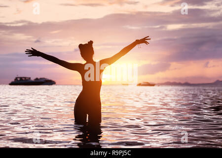 Silhouette of happy slim girl stands in tranquil water with raised arms and greeting sunset - Stock Photo