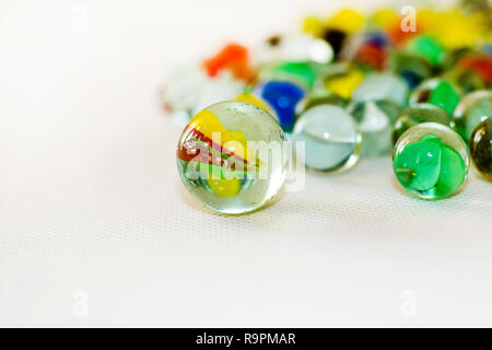 Vintage marbles on white backdrop and blurred out background. - Stock Photo