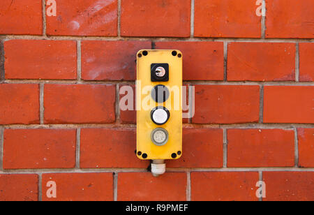 Industrial yellow switch box with power on and off switches buttons and key lock installed outdoors on a red brick wall from warehouse. - Stock Photo