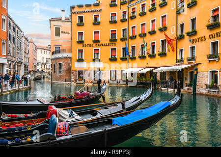 A gondolier maneuvers his gondola in the dock of the Orseolo Basin in front of a luxury hotel as tourists enjoy a late afternoon in Venice, Italy - Stock Photo