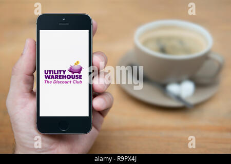 A man looks at his iPhone which displays the Utility Warehouse logo (Editorial use only). - Stock Photo