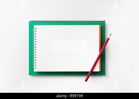 Design concept - Top view of green and red spiral notebook and pencil isolated on background for mockup - Stock Photo