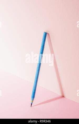 a blue pencil. Pink Two Tone Background. - Stock Photo
